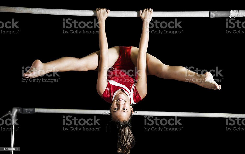Strong gymnast girl exercising on uneven bars. stock photo