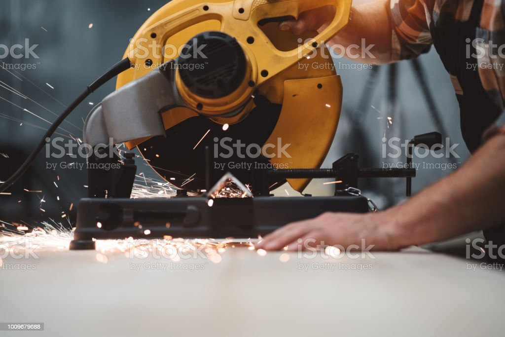 Strong hands of mechanic working on electrical angular grinding machine at metalworking factory, sparks fly apart. Work in process on plant. Horizontal. Flare effect stock photo