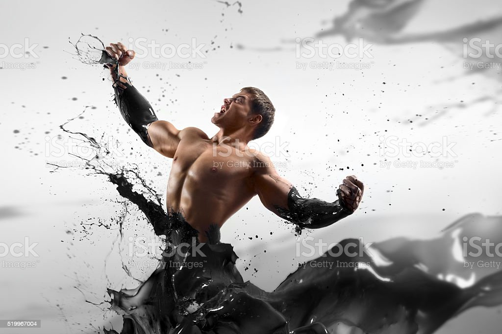 Strong handsome man on an abstract background oiled stock photo