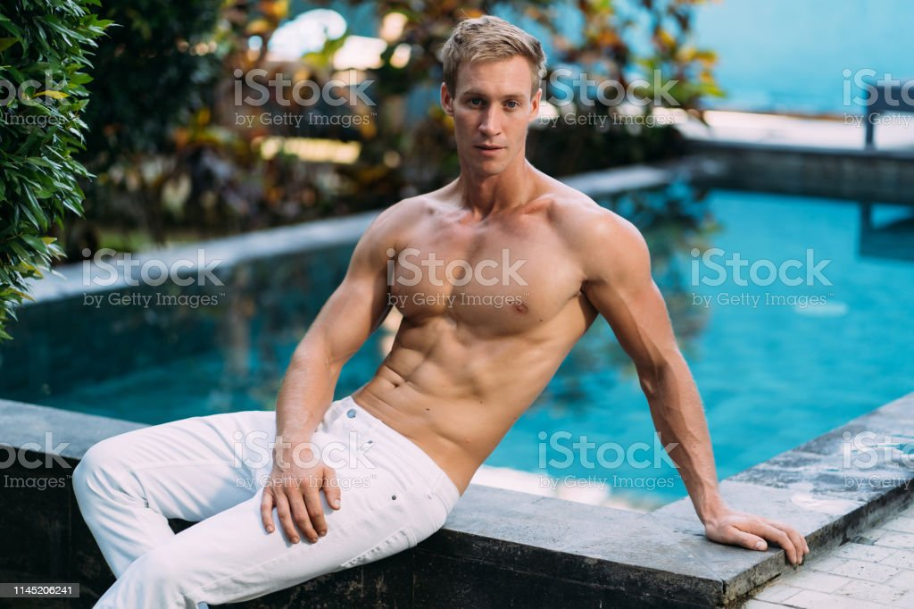 Strong handsome shirtless man in white pants sits on pool in garden....