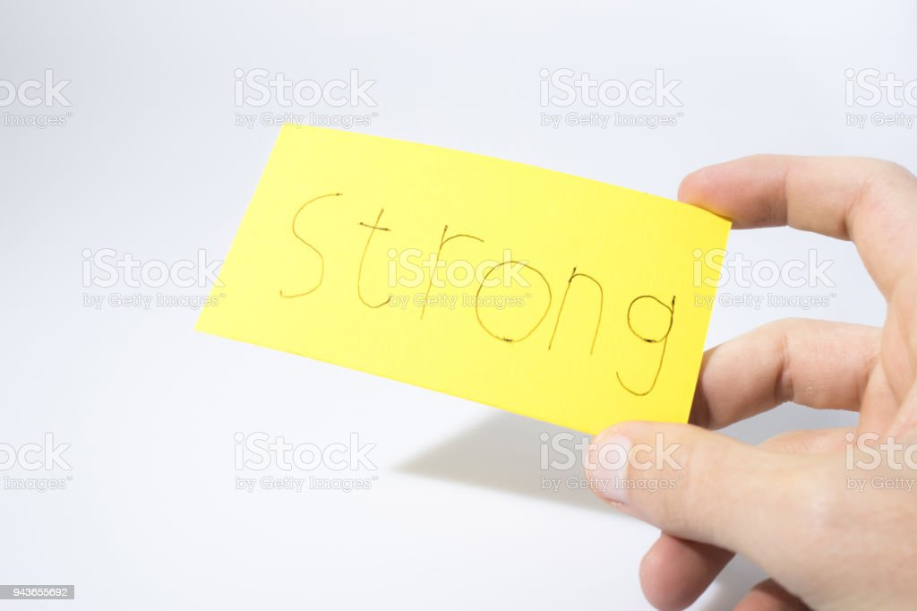 Strong handwrite with a hand on a yellow paper composition stock photo