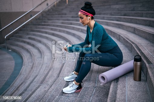1091470492 istock photo Strong healthy woman using her mobile phone while sitting on the stairs in a downtown urban area 1082376030
