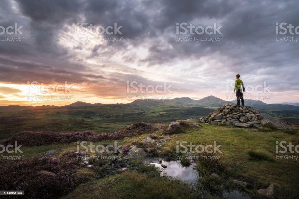 Sterke wandelaar gelukkig en genieten van de zonsondergang over Lake District Engeland berg achtergrond foto