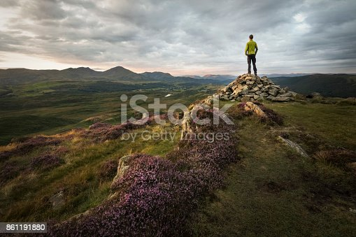 istock Strong hiker overlooking the beautiful mountains of the lake district at sunset with sunlight lit purple heathland 861191880