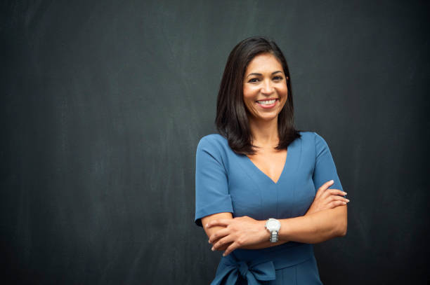 Strong Hispanic Woman Teacher Hispanic woman with chalk board background for copy space. latin american and hispanic ethnicity stock pictures, royalty-free photos & images
