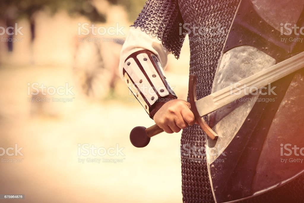 strong knight hand with beautiful sword and shield on the middle ages decoration background stock photo