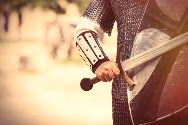 strong knight hand with beautiful sword and shield on the middle ages decoration background - foto de stock