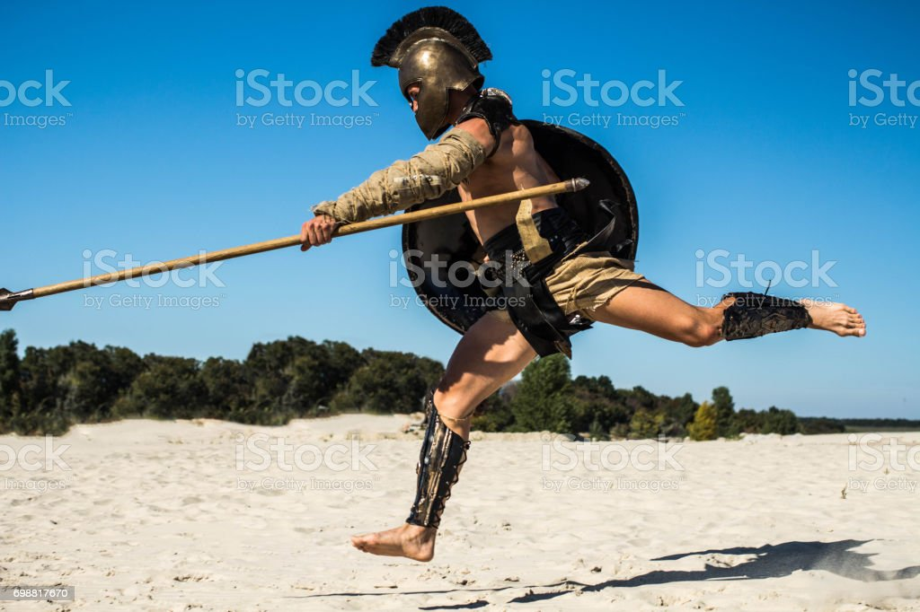 Strong legionnaire's legs in a jump on the opponent stock photo