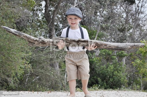Strong little boy carries a big log as he walks along the beach.