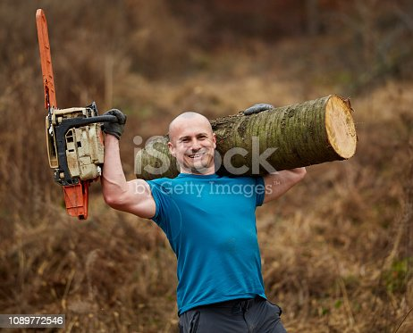 Strong muscular lumberjack with chainsaw, carrying a huge log on his shoulder