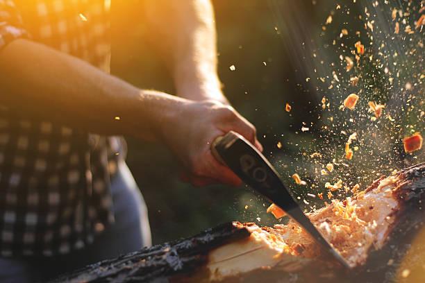 strong lumberjack chopping wood, chips fly apart - macho fotografías e imágenes de stock