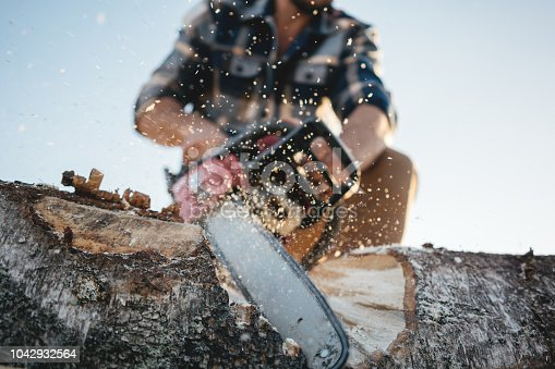Strong lumberjack wearing plaid shirt and hat use chainsaw in sawmill. Sawdust fly apart