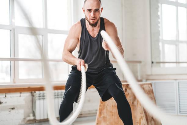 Starke männliche Athleten, die Übungen mit Seil in der Turnhalle. Training mit Kampfseilen im Cross-Gymnastik – Foto