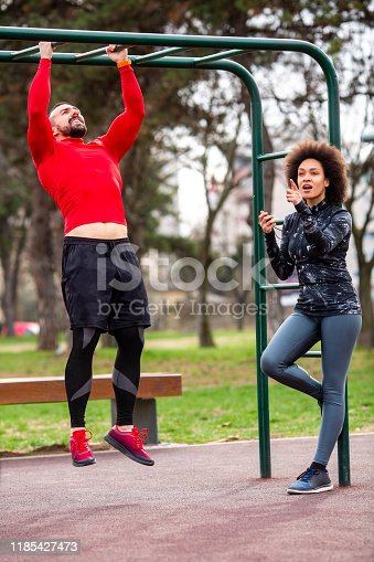 Strong athletic male doing pull-ups on monkey bars in a public park with his personal fitness trainer standing next to him and measuring his performance.