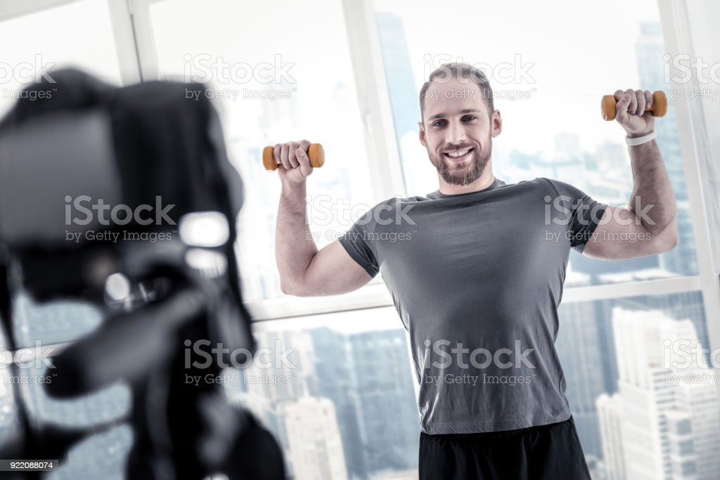 Strong male blogger perfecting biceps stock photo