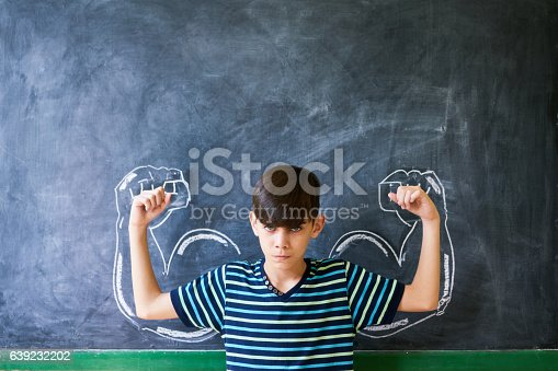 istock Strong Male Child Showing Muscles In Classroom At Lesson 639232202