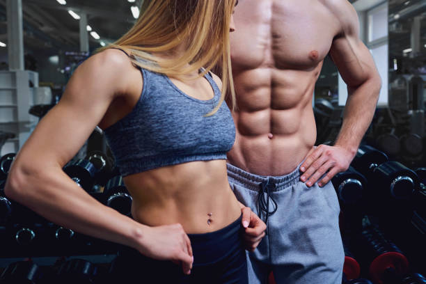 Strong man and a woman are posing with beautiful bodies. Strong man and a woman are posing with beautiful bodies. Sports couple in the gym. abdominal muscle stock pictures, royalty-free photos & images