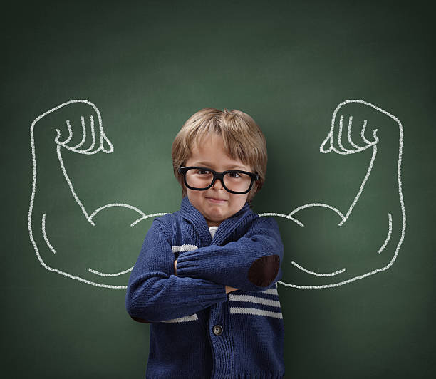 Strong man child showing bicep muscles stock photo
