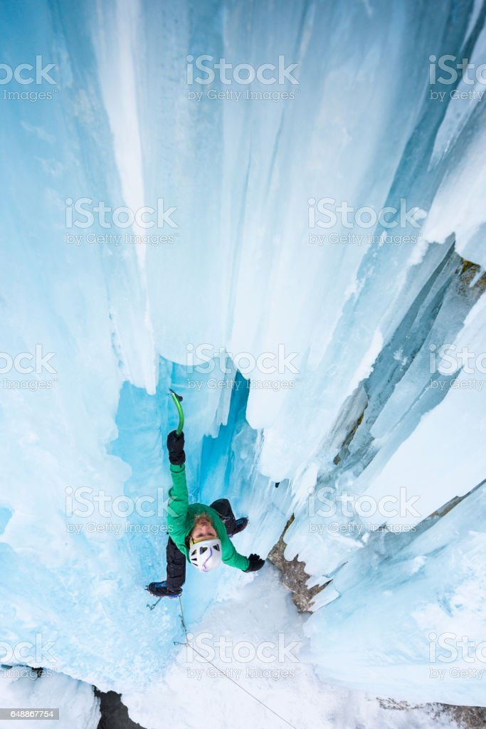 Strong man climbing on blue icicles outdoor stock photo