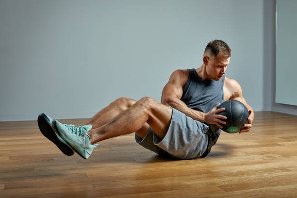 Strong man doing exercise with med ball. Photo of man perfect physique on grey background. Strength and motivation stock photo