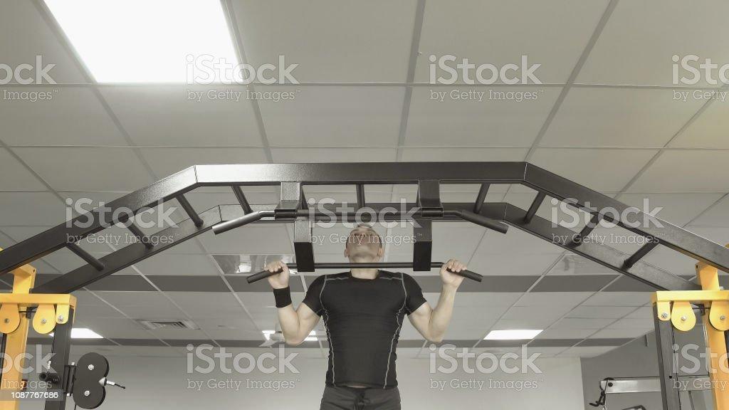 Starker Mann tun Pull ups in einem Fitnessstudio – Foto