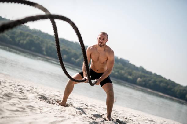 starker mann dabei training mit schlacht seil - sachenmacher stock-fotos und bilder