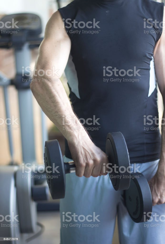 Strong man in 40's gym weight training with dumbells to gain muscle mass and get fit in exercise program training. stock photo