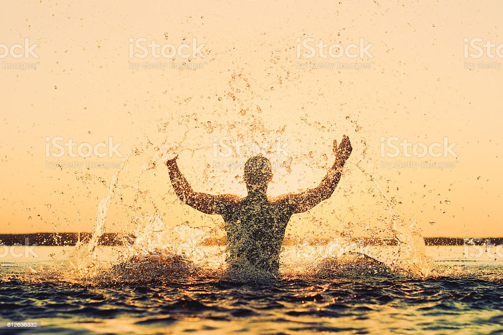 Strong man in a spray of water at sunset stock photo