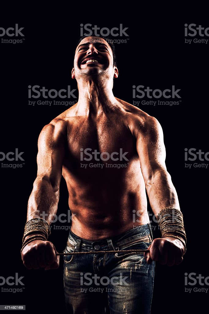 Strong man in studio tied with rope royalty-free stock photo