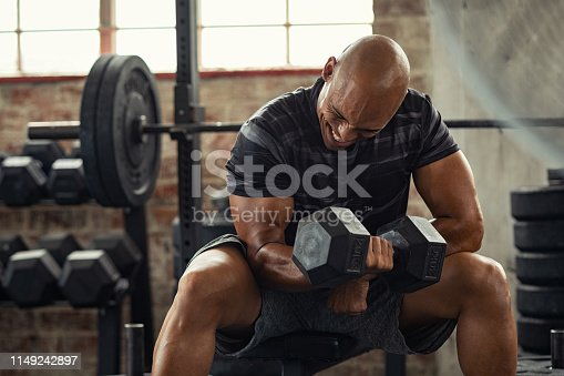 Muscular guy in sportswear lifting dumbbell while sitting on bench at cross training gym. Mature african american athlete using dumbbell during a workout. Strong man under physical exertion pumping up bicep muscule with heavy weight.