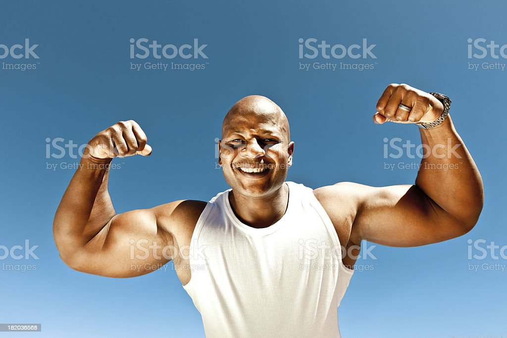 Strong man Muscular man showing his biceps against clear blue sky, smiling at camera. Active Lifestyle Stock Photo