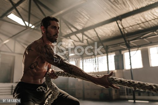 istock Strong man pulling heavy rope at gym 911813374