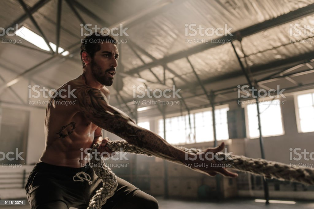 Strong man pulling heavy rope at gym stock photo