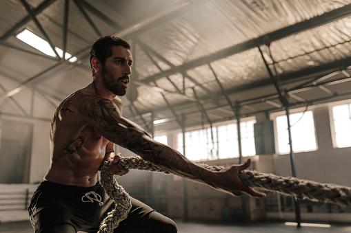 Foto de Homem Forte Puxando A Corda Pesada No Ginásio e mais fotos de stock de Academia de ginástica