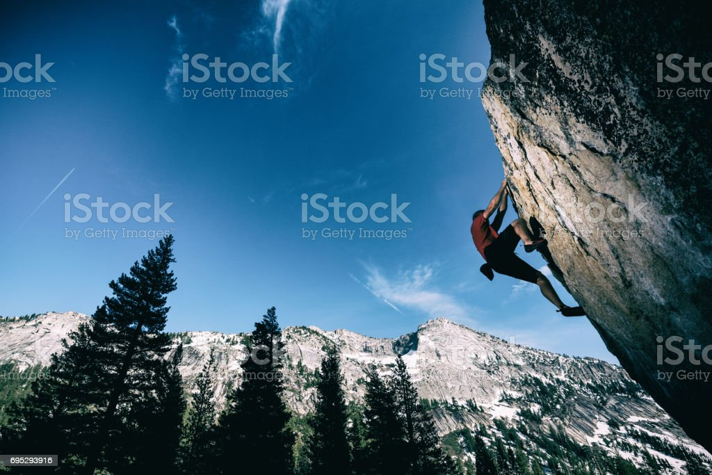 Strong man reaching for the top of a boulder stock photo