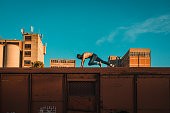 istock Strong man running and jumping on the top of the train wagon 1138942122