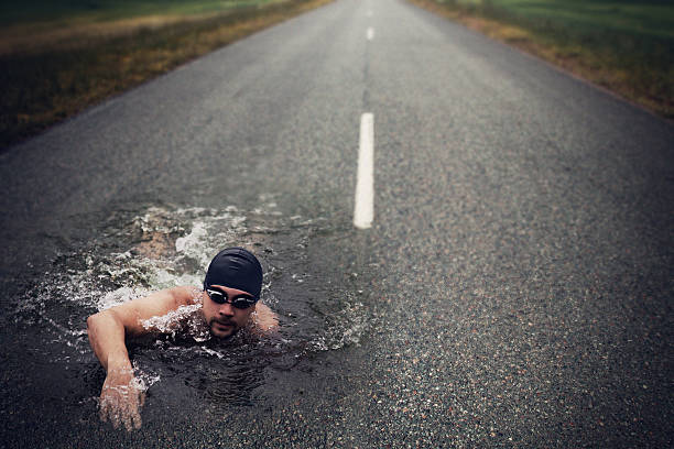 strong man swim on asphalt road - conquering adversity stock photos and pictures