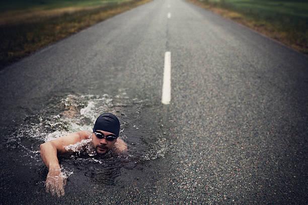Strong Man Swim On Asphalt Road stock photo