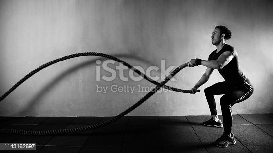 Strong man training with battle rope at gym