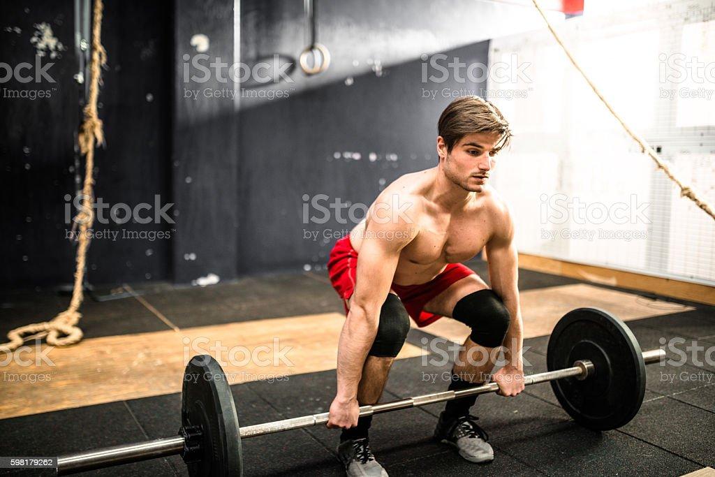 Homem forte de musculação uma barra foto royalty-free