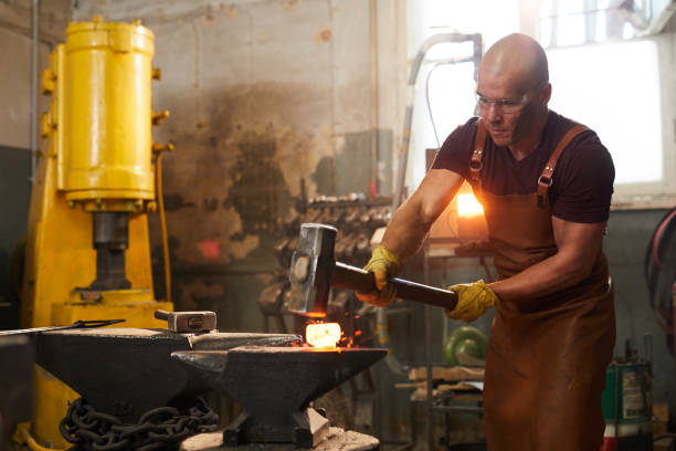 Strong man working in smithy Strong young man in safety goggles and apron using sledgehammer to shape metal piece while working in smithy anvil stock pictures, royalty-free photos & images