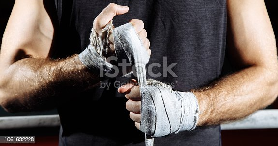 istock Strong man wrap hands on black background. Man is wrapping hands with boxing wraps, ready for training and active exercise. 1061632228