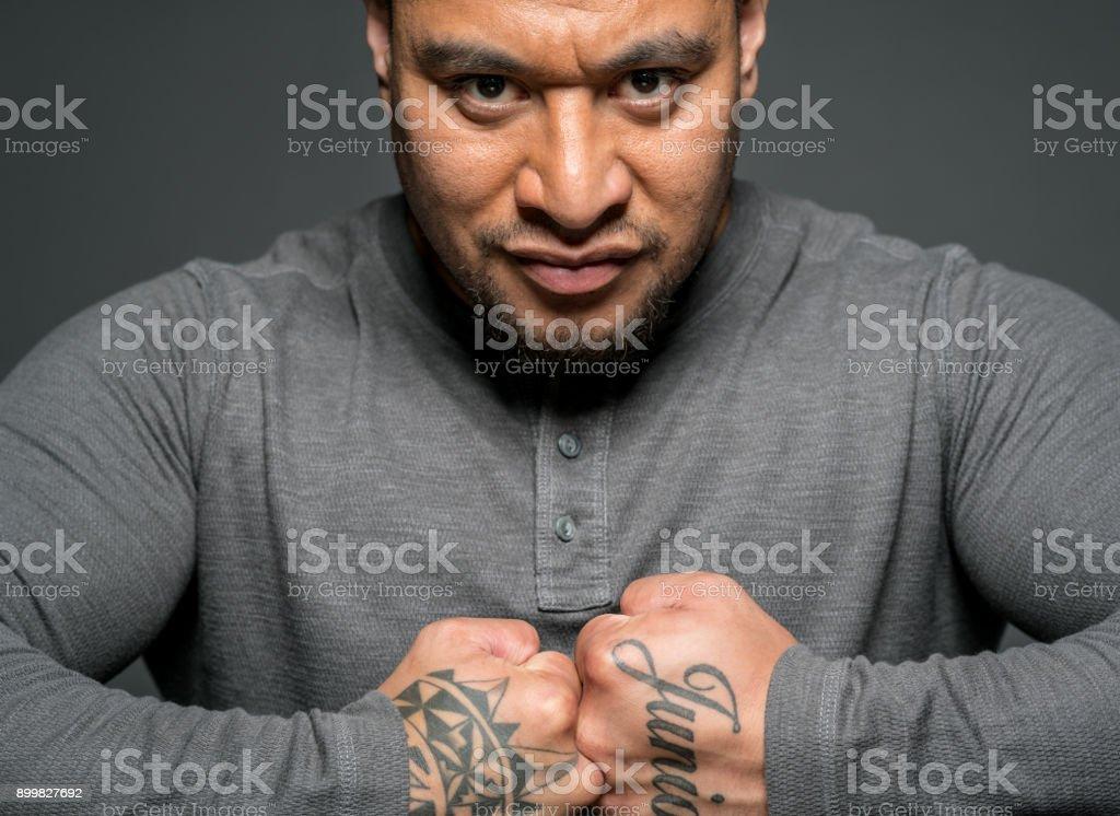 Strong Maori man showing his tattoos - Stock image .
