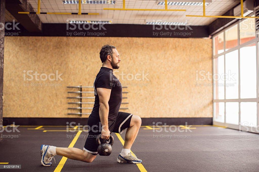 Fuerte maduro hombre anciano haciendo se pone en cuclillas con pesa rusa - foto de stock