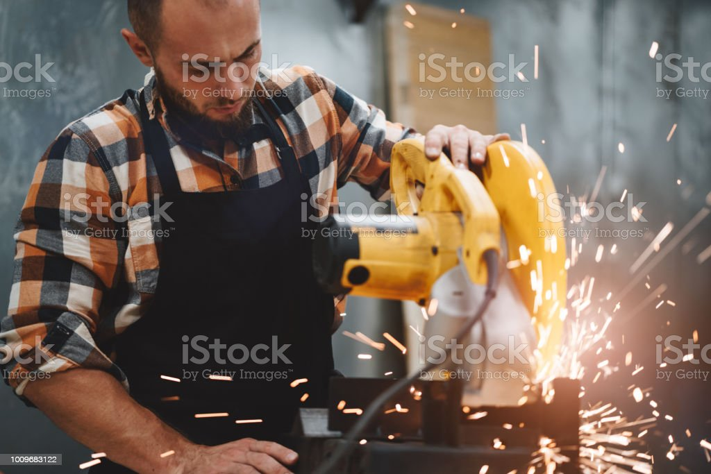 Strong mechanic working on electrical angular grinding machine at metalworking factory, sparks fly apart. Work in process on plant. Horizontal. Flare effect stock photo