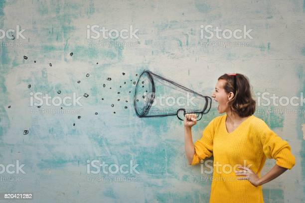 Young woman holding an imaginary megaphone and shouting into it