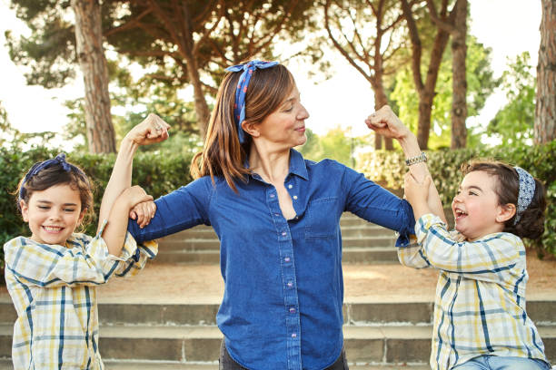 Strong mom flexing her arms - Girl power stock photo