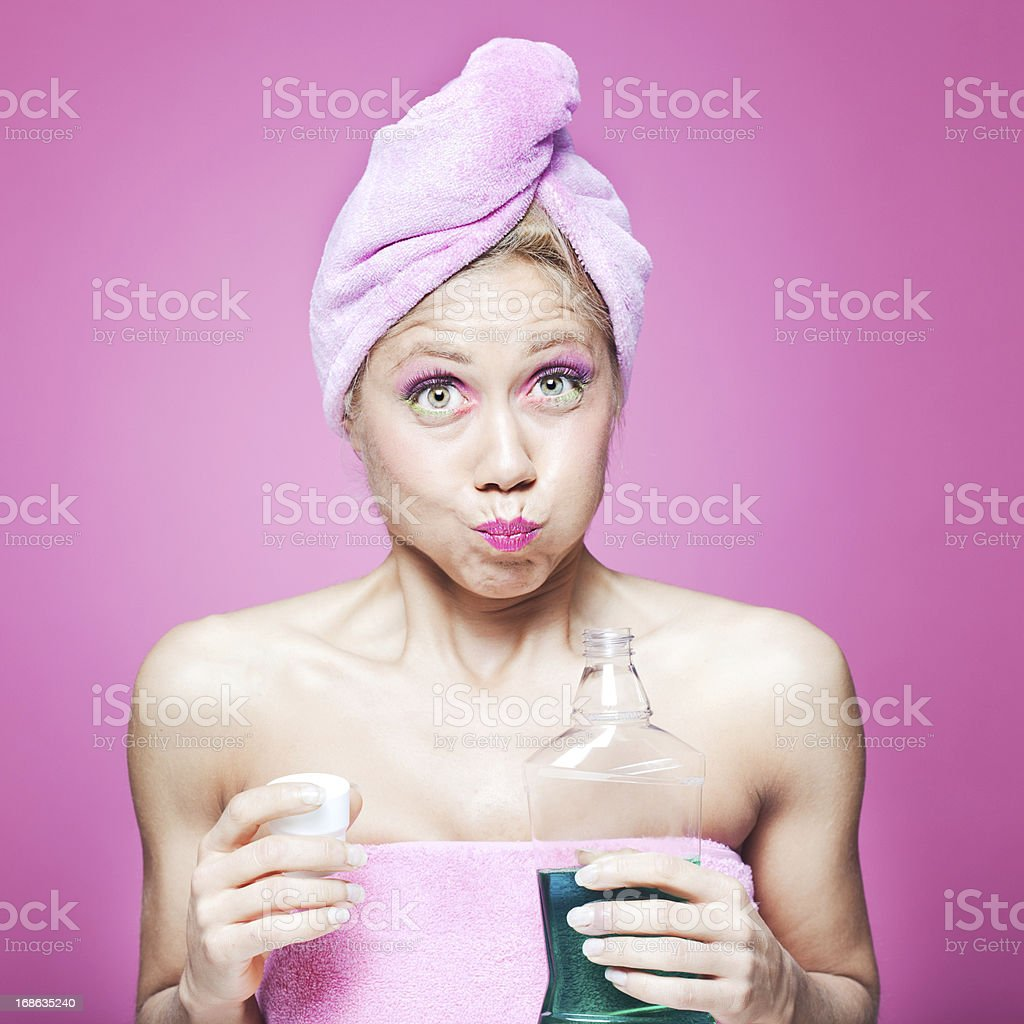 One young woman with mouthwash in the bathroom. More files of this...