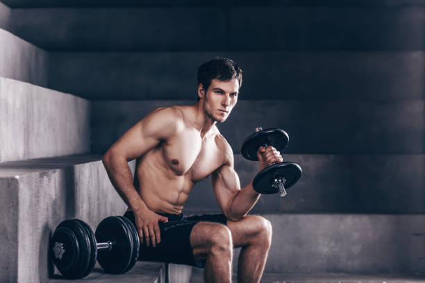 Strong muscle man sit and exercise biceps with heavy dumbbells. stock photo