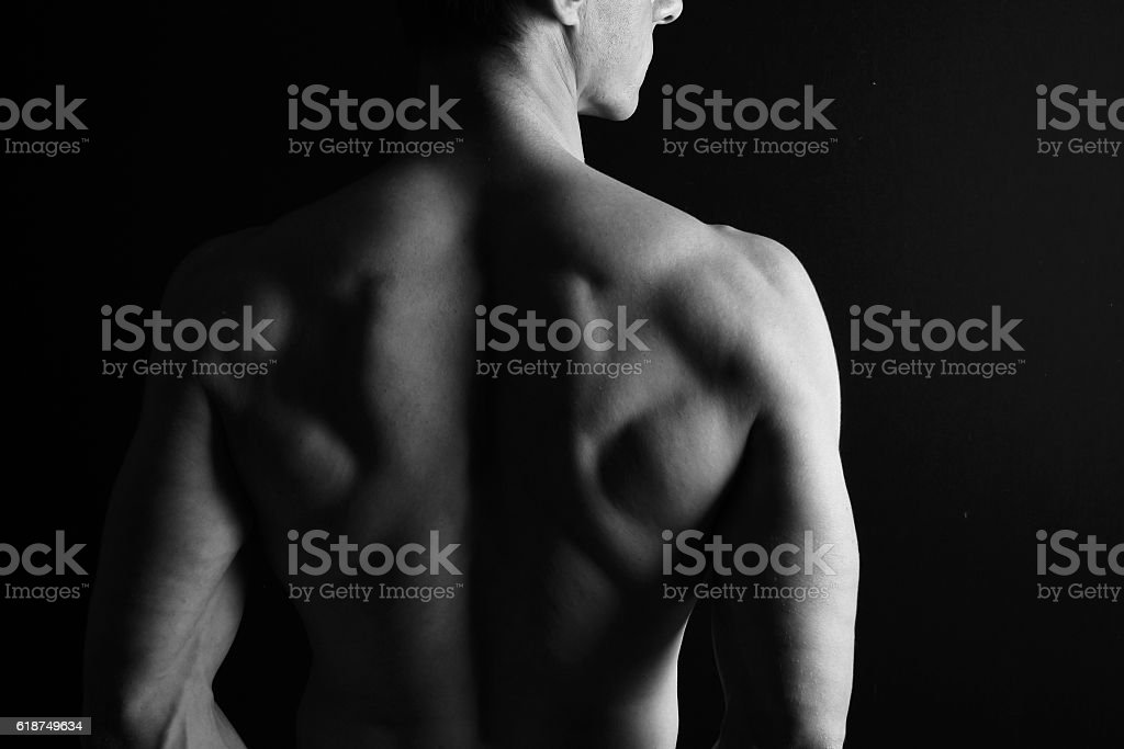 Strong muscular athletic man back on dark background stock photo